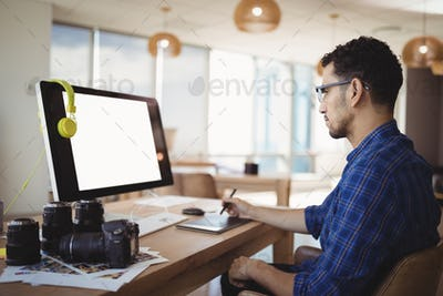 Attentive graphic designer using graphic tablet at desk