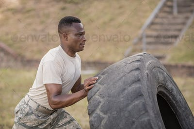 Determined military soldiers exercising with tyre