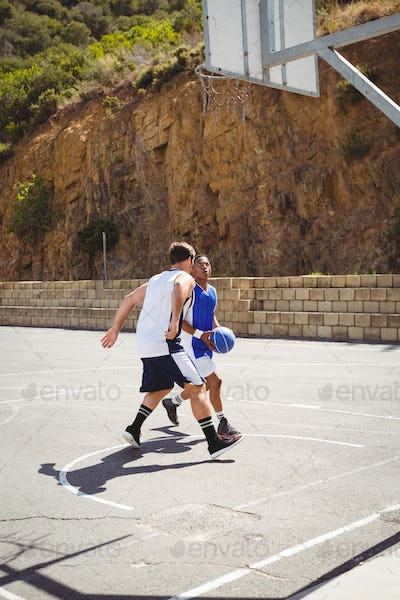 Full length of friends playing basketball
