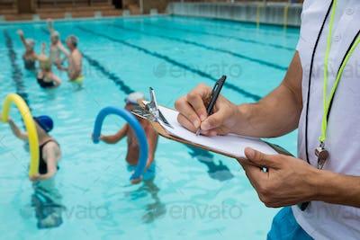 Swim coach writing on clipboard near poolside