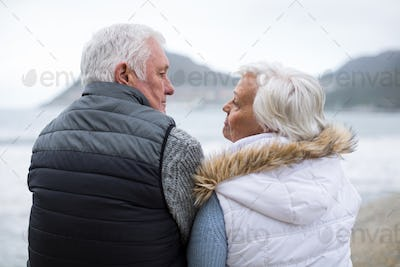 Senior couple sitting on rock at beach