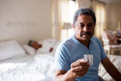 Sick senior man looking at medicine packet in bedroom