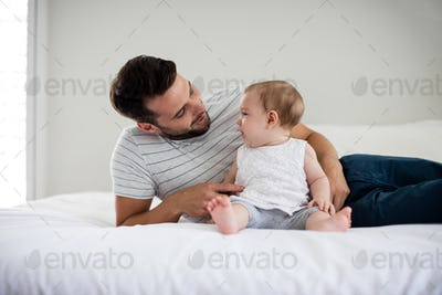 Father playing with his baby girl in bedroom