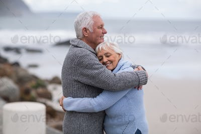 Senior couple embracing each other on the beach