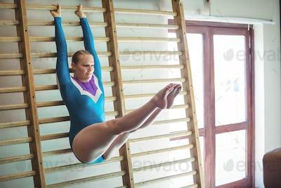 Female gymnast practicing gymnastics on wooden wall bar