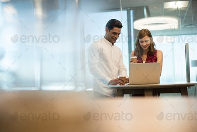 Business people having coffee while using laptop in office
