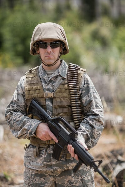 Confident military soldier standing with rifle