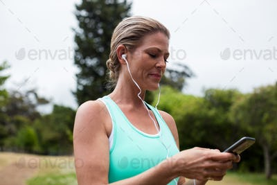 Female athlete listening to music on mobile phone