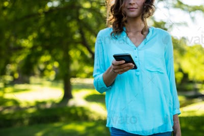 Mid-section of woman using mobile phone