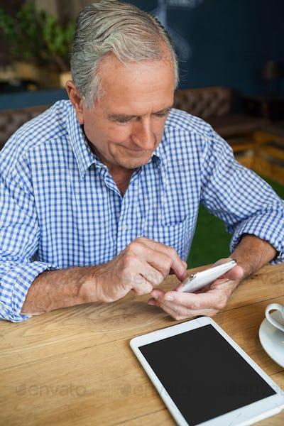 High angle view of senior man using smart phone at table