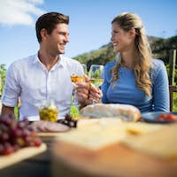 Happy couple looking at each other while holding wineglasses at vineyard