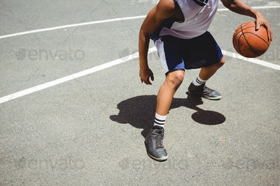 Low section teenage boy practicing basketball at court