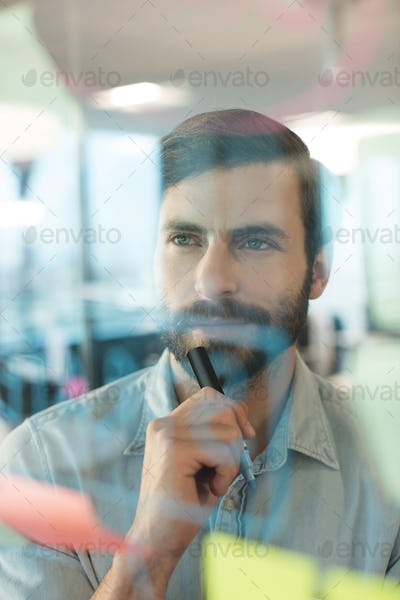 Thoughtful businessman looking at plans written on glass