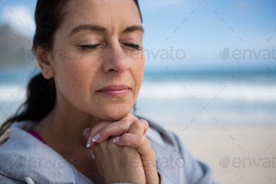 Mature woman praying with hands clasped