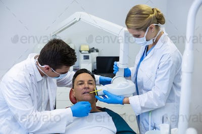 Dentists examining a male patient with tools