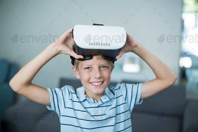 Portrait of boy holding virtual reality headset in living room