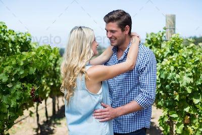 Smiling young couple embracing at vineyard