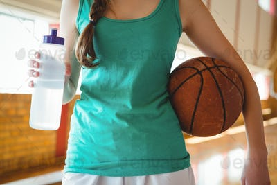 Midsection of female basketball player with bottle in court