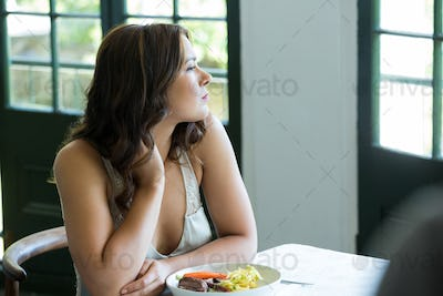 Thoughtful woman sitting at restaurant table
