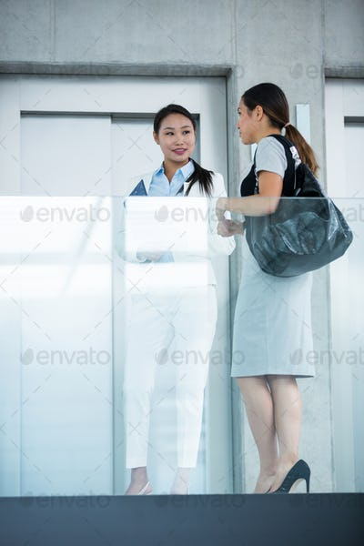 Businesswomen standing by elevator and having a conversation