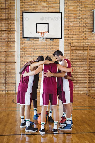 Basketball players forming a huddle