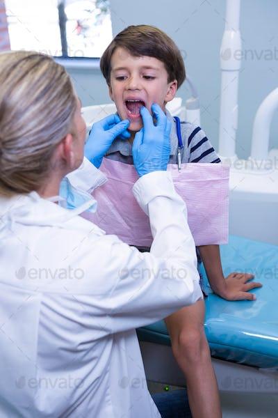 Dentist examining boy at dental clinic