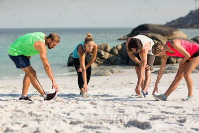 Young friends exercising on shore at beach