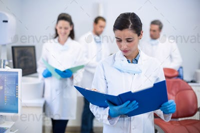 Dentist looking at reports in dental clinic