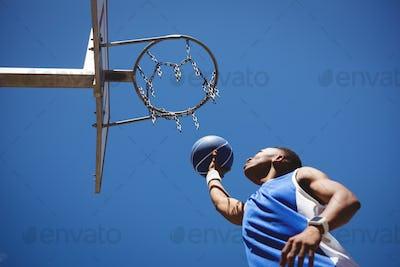 Low angle view of teenage boy playing basketball