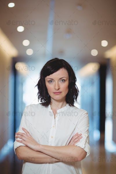 Portrait of female executive standing with arms crossed in corridor
