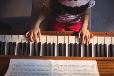 Overhead view of girl practicing piano in classroom