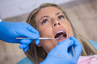 Dentist examining a female patient with tools