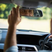 Man adjusting mirror in car