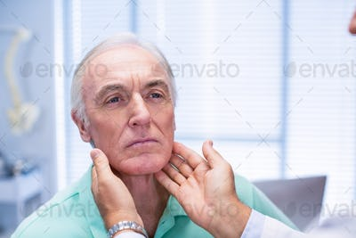 Doctor examining senior patients neck