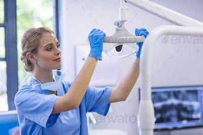 Female nurse adjusting dental light