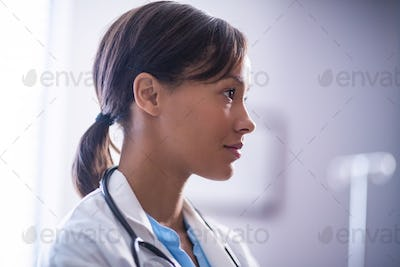Thoughtful female doctor with stethoscope in ward