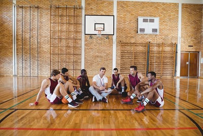 Coach explaining game plan to basketball players