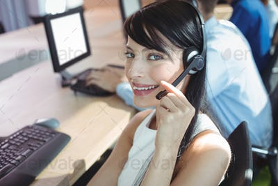 Portrait of young businesswoman using headset