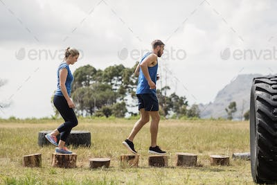 Fit woman and man running on wooden logs during obstacle course