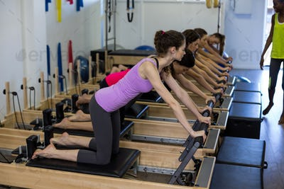 Female trainer assisting group of women with stretching exercise on reformer