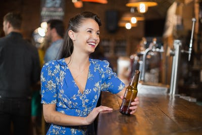 Happy woman looking away while holding beer bottle