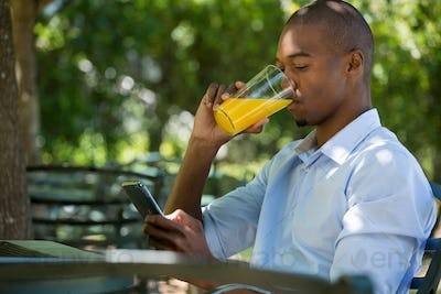 Man drinking juice while using mobile phone at restaurant