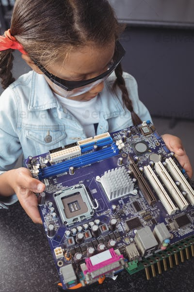 High angle view of concentrated elementary student examining circuit board