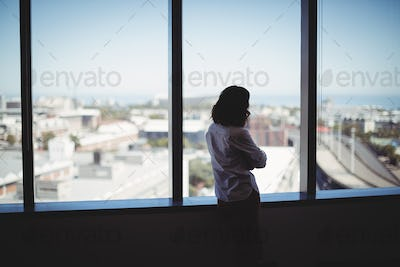 Female business executive looking through window