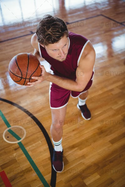 High angle view of male player practicing basketball