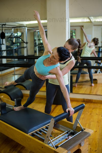 Female trainer assisting woman with stretching exercise on reformer