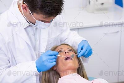 Dentist examining woman at dental clinic