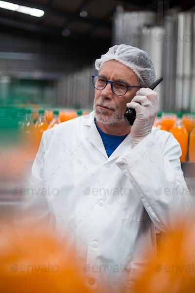 Factory engineer talking on walkie talkie