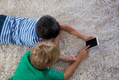 Siblings lying on rug and using mobile phone in living room
