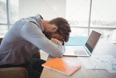 Tired executive leaning on desk